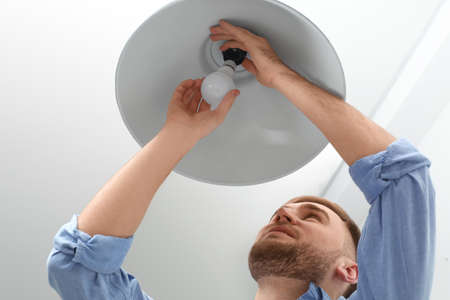 Man changing light bulb in lamp indoors Stockfoto