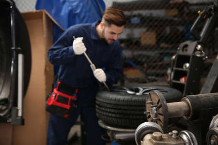 Technician working with car wheel at automobile repair shop