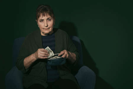 Poor senior woman with money on color background. Space for text