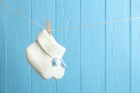 Baby booties on laundry line against color wooden background, space for text. Child accessories Stock Photo