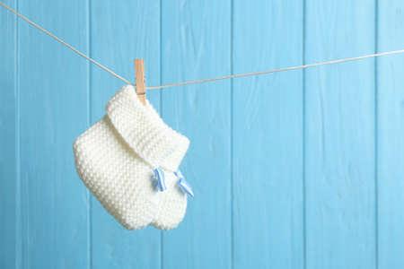 Patucos de bebé en la línea de ropa contra el color de fondo de madera, espacio para texto. Accesorios para niños Foto de archivo