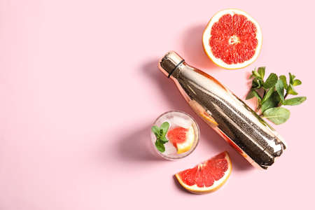 Flat lay composition with glass of infused water, grapefruits and bottle on color background. Space for text