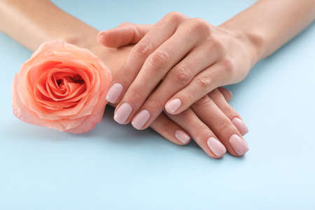 Closeup view of woman with rose on color background. Spa treatment