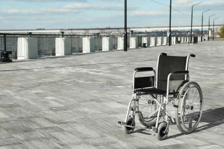 Empty wheelchair outdoors on sunny day. Space for text