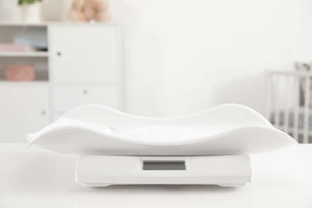 Modern digital baby scales on table in room. Space for text