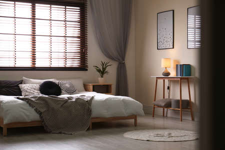 Modern room interior with comfortable double bed and window blinds