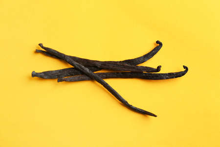 Bunch of aromatic vanilla sticks on yellow background