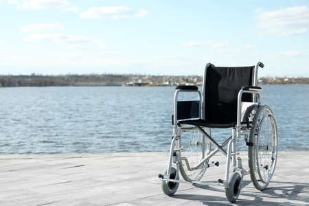 Empty wheelchair near river on sunny day. Space for text Imagens