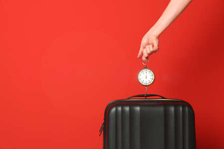Woman weighing suitcase against color background, closeup. Space for text Imagens - 122430679