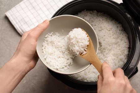 Donna che mette il riso nella ciotola dal fornello in cucina, vista dall'alto