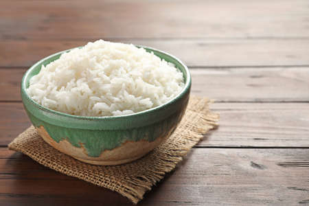 Bowl of tasty cooked white rice on wooden table. Space for text 版權商用圖片