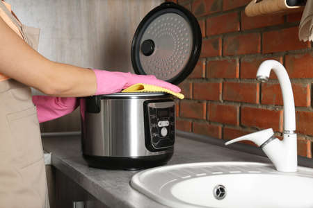 Young woman cleaning modern multi cooker in kitchen, closeup Banco de Imagens