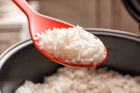Spoon with tasty hot rice over cooker, closeup