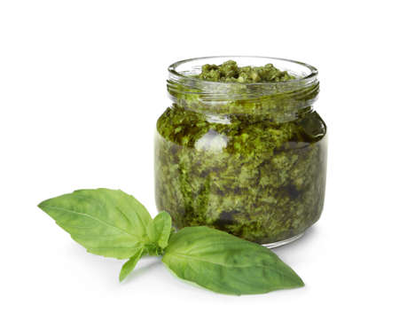 Jar of tasty pesto sauce and basil leaves isolated on white 写真素材