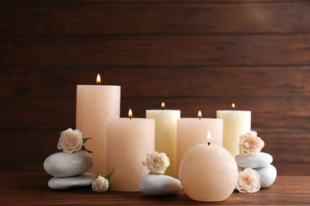 Samenstelling van brandende kaarsen, spa-stenen en bloemen op tafel. Ruimte voor tekst Stockfoto
