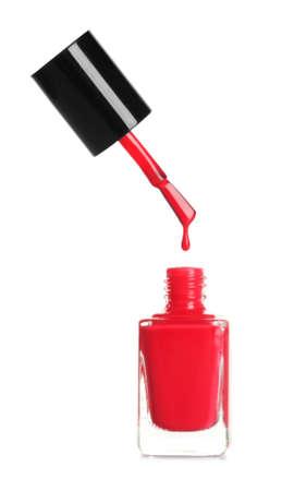 Brush over nail polish bottle on white background