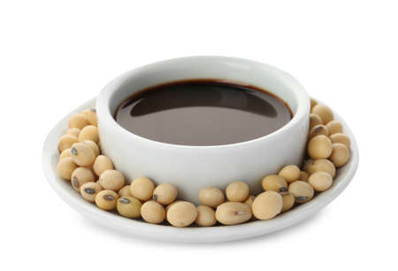 Dish of soy sauce with beans on white background