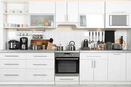 Different appliances, clean dishes and utensils on kitchen counter Reklamní fotografie