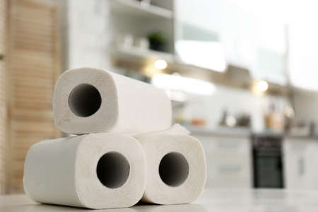 Rolls of paper towels on table in kitchen, space for text