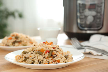 Delicious rice with vegetables on wooden table, closeup. Multi cooker recipes