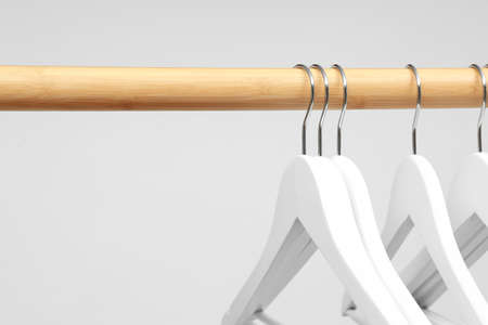 Empty clothes hangers on wooden rail against light background, closeup. Space for text