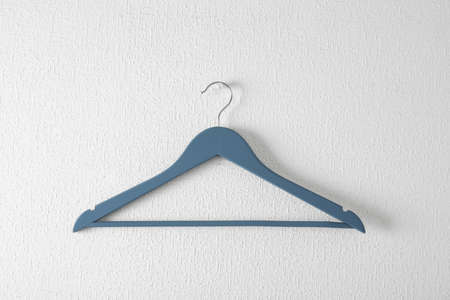Empty clothes hanger on light wall. Wardrobe accessory