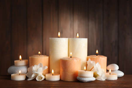 Beautiful composition with candles, flowers and stones on table against wooden background