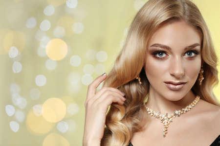 Bella giovane donna con gioielli eleganti contro luci sfocate. Spazio per il testo