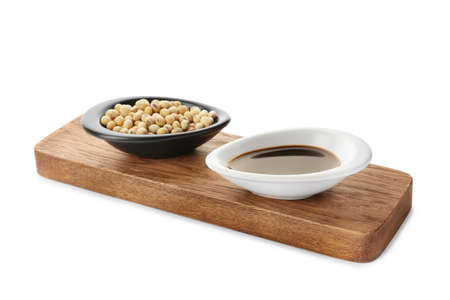 Wooden board with dishes of soy sauce and beans on white background Stock Photo