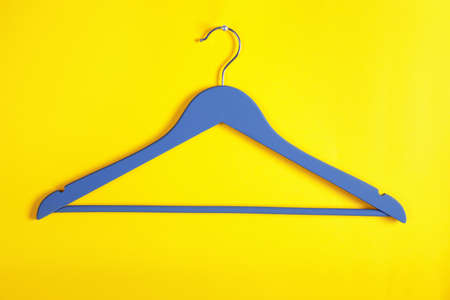 Empty clothes hanger on color background. Wardrobe accessory Stock Photo