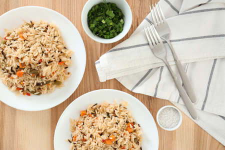Delicious rice with vegetables served on wooden table, flat lay. Multi cooker recipes