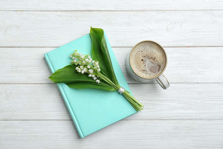 Flat lay composition with notebook, lily of the valley bouquet and coffee on white wooden background