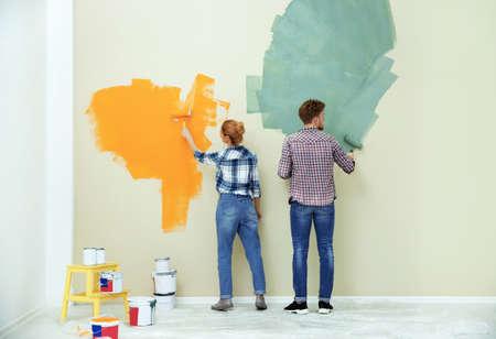 Pareja joven pintando la pared en el interior. Reparaciones en el hogar Foto de archivo