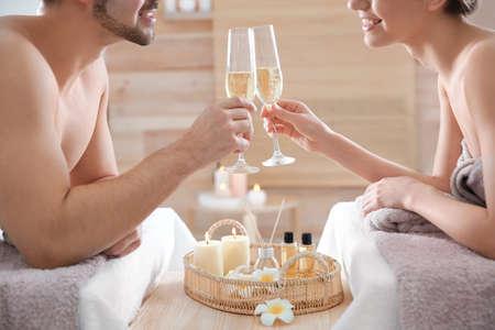 Giovani coppie romantiche con champagne nel salone della stazione termale, primo piano Archivio Fotografico