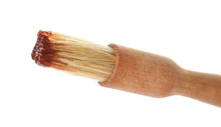 Basting brush with barbecue sauce on white background