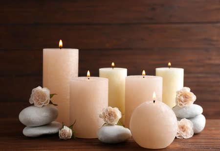 Composición de velas encendidas, piedras de spa y flores sobre la mesa. Espacio para texto Foto de archivo