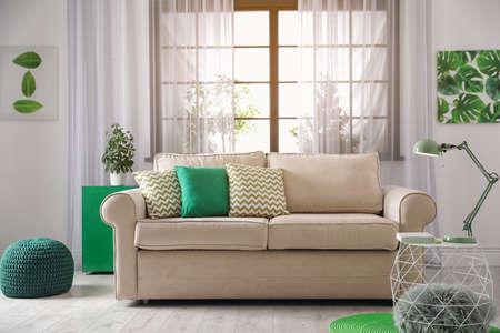 Comodo divano vicino alla finestra nell'interno moderno del soggiorno