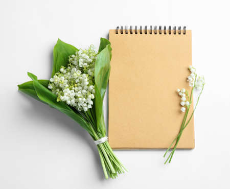 Notebook and lily of the valley bouquet on white background, flat lay. Space for text