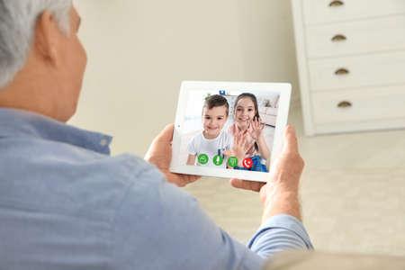 Vista in primo piano dell'uomo anziano che parla con i nipoti tramite chat video a casa Archivio Fotografico