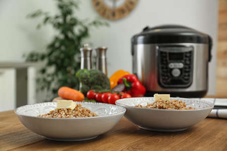 Two plates with delicious buckwheat and modern multi cooker on wooden table