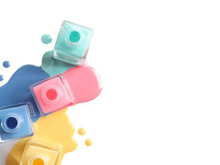 Différents vernis à ongles renversés avec des bouteilles sur fond blanc, vue de dessus