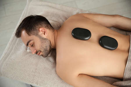 Handsome man receiving hot stone massage in spa salon, top view Imagens
