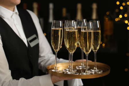 Waiter holding tray with glasses of champagne on blurred background, closeup Stock Photo