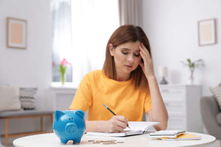 Sad woman with piggy bank and money at table indoors