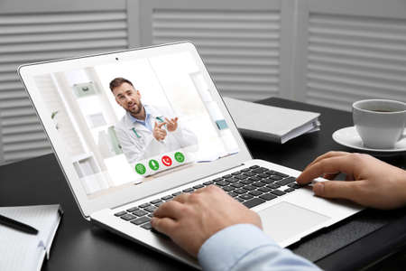 Man using laptop for online consultation with doctor via video chat at table, closeup Foto de archivo