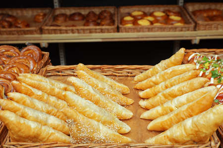 Tray with fresh puff pastry turnovers on bakery showcase