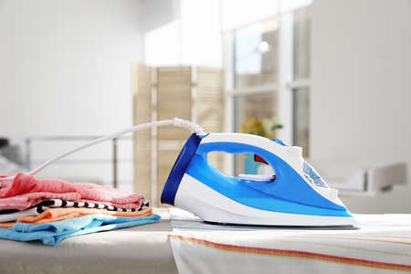 Modern electric iron on board indoors, space for text. Household appliance