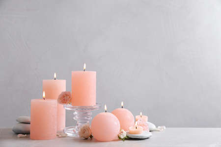 Beautiful composition with candles on table against grey background. Space for text