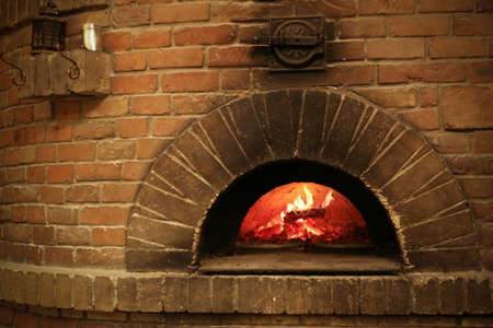 Brick oven with burning firewood and pizzas indoors Stockfoto