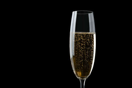 Glass of fizzy champagne on black background, closeup. Space for text